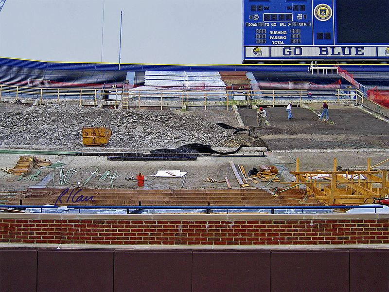 Reconstruction of spectator seating. Upper portion is new seating.  Left middle is demolished old concrete, waiting for removal.  Workers at mid-right are hand grading soil base for new concrete seating base. Formwork for new concrete base is being erected in lower section of seating area. The Big House, Michigan Stadium, University of Michigan, Ann Arbor, 2004.