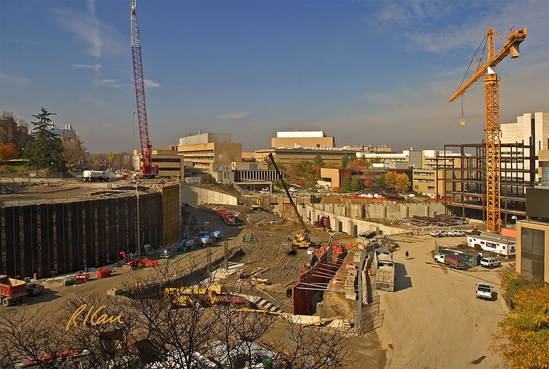 Building Construction: Two large segments of a large building site: Retaining wall and foundation construction to left and structural steel construction to right. Mobile crawler crane serves the left, and tower crane serves the right.  Mobile hydraulic crane serves center foundation area. A second hydraulic crane behind building to far right cannot be seen here. Cardiovascular Center, University of Michigan Hospital, Ann Arbor, 2004.