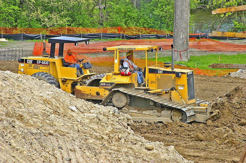 Bridge construction: Caterpillar D6M 140 horsepower, 15.5 ton crawler tractor bulldozer. In background is Caterpillar CP-563C single drum padfoot vibratory soil compactor. Broadway Bridge, Ann Arbor, 2003.