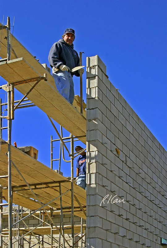 "Masonry construction, safety: Bricklayer holding trowel and level erects end block on wall. The mason stands on 2-2""x10"" wood planks supported by side brackets attached to vertical tubes of welded tubular steel walk-thru scaffold. Mason is unsafe, because he is exposed to 20' fall without fall protection.<br /> <br /> 5-2""x10"" planks form material platforms below and above, just behind mason, on which mortar boxs, mortar boards, and stacks of concrete block are placed to provide masons the materials they need to erect wall. <br /> <br /> Extending out from the exterior side of concrete block wall are the corrugated steel wire eye segment of a 2-piece adjustable tie system into which the pentile segment embedded in the mortar of the brick veneer exterior wall surface to provide lateral support (support against wind) to the brick. Ann Arbor, 2004."