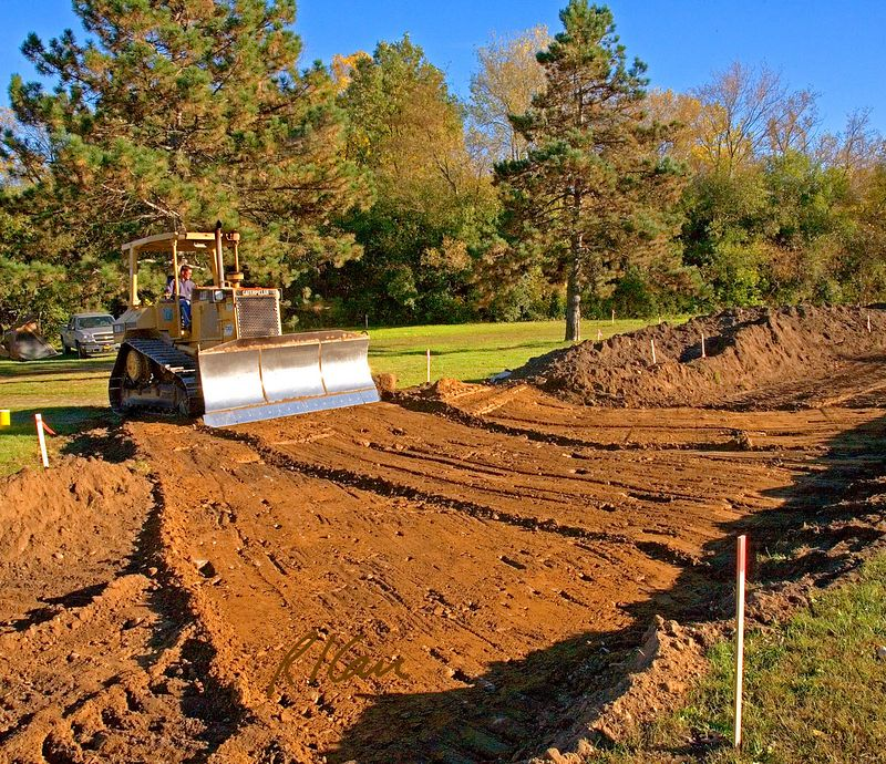 Soil construction, earth moving: Caterpillar D5M 110 hp track mounted bull dozer backs up using backside of dozer blade to rough grade the future roadbed. Huron Parkway, Ann Arbor, Michigan 2005.