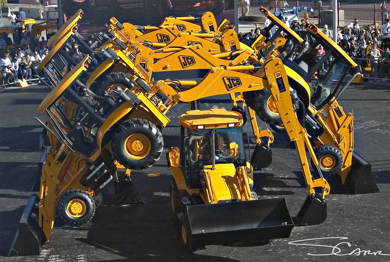 Earthmoving construction: First day of CONEXPO 2005. JCB Dancers form arch with JCB backhoe-loader excavators. Las Vegas, Nevada, March 15, 2005.