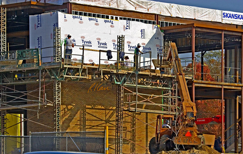 Masonry construction: Lull 8K-42 rough terrain forklift lifts and places mortar box on material platform of Hydro-Mobile self-lifting scaffold. Worker on scaffold holds left guardrail gate open after already having opened right guardrail gate. Bricklayers standing on the bricklayer level are laying brick. Lull 8K-42 has 4-wheel drive, 3-way steering, and 8,000 lb capacity, and its hydraulic telescoping boom has 42 ft reach. Biomedical Engineering, North Campus, University of Michigan, Ann Arbor, 2004.