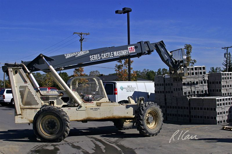 "Masonry construction: Terex SS-842 rough terrain hydraulic telescopic boom forklift picks up banded batch of 8""x8""x16"" concrete blocks, using the left two tines of its fork. Forklift has 8,000 lb capacity and can reach 25' and lift 42' high. Huron Village Shopping Center, Ann Arbor, 2004."