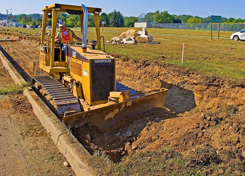 Earth moving construction: Caterpillar D4C track mounted tractor bull dozer excavates earth for underground construction alongside parkway. Earth is dozed to this end of trench, where a backhoe loads it into dump trucks to haul away. Huron Parkway at Huron High School, Ann Arbor, Michigan August 2005