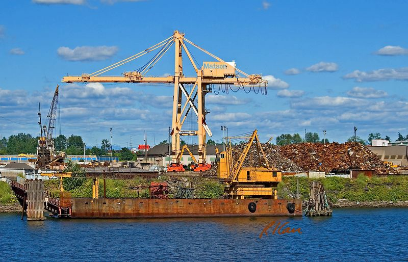 Scrap metal yard and cranes: Scrap steel pile on right side of photo is transferred between scrap heap and barges/ships at loading dock. Primary crane is large Mitsui Paceco 40 ton rail mounted gantry crane that dominates the site. Rotary mounted cabled operated truss boom crane is at loading dock. Oregon, Coluimbia River, 2005