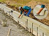 Concrete construction, road/street construction: Worker uses grooving tool to cut control joint into fresh concrete. The control joint introduces a plane of weakness through the curb, so that if the curb concrete should crack, the crack will form at the control joint, rather than at random. The worker will next use his trowel to smooth out the rough line left by the outside edge of the tool. Notice other control joints already created. Huron Parkway at Huron High School, just North of Geddes, Ann Arbor, Michigan 2005.