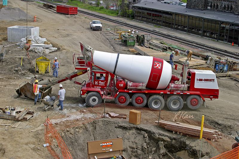 Bridge concrete construction: Readymix truck's rotating drum dumps freshly mixed concrete into the truck's chute. <br /> Concrete flows into the layed down concrete bucket. Broadway Bridge, Ann Arbor, 2003.