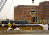 Concrete construction: Concrete is placed for bridge from lay-down concrete bucket supported by crane. Worker pulls down on pipe handle for concrete valve at bottom of bucket. Workers in mid/foreground are installing cover on freshly placed concrete to protect it from rapid cooling and drying. Woodrow Wilson Bridge; Project; George Washington Street, Alexandria, Virginia, November 2006