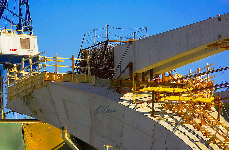 Construction of the cast in place concrete connection between one end of V-shaped bridge pier and one end of concrete tension beam, which ties two ends of bridge pier together to carry their outward thrust. The key element is the tightly grouped reinforcing steel in the center of the photo. Wood forms will be built around the reinforcing steel, and ready-mix concrete will be placed to fill the forms around the steel. After this concrete has gained its strength, post-tensioning cables run through the white tubes will be tensioned strongly to connect the tie beam to the bridge pier. In the interim, highly stressed tension cables, circled in blue, provide support against outward thrust of the piers until the tension beams are completed. Woodrow Wilson Bridge replacement, Potomac River between Virginia and Maryland, Capitol Beltway, I-95/I-495. November 2006.