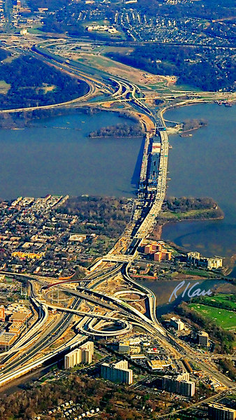 Airplane view of Woodrow Wilson Bridge construction project, looking from west to east, wiith the bridge carrying the Capital Beltway US495 and the Potomac River it spans in the center. The bridge shows three distinct segments. On the left are remains of the two lane westbound segment of the old bridge, not yet fully dismantled. In the center, dark in color, is the four lane westbound segment under construction. On the right are the four lanes of the new eastbound segment, currently carrying two lanes each way until the new westbound segment is completed. At photo bottom is the highway interchange between Route 1 and Capital Beltway I 95/495 with scheduled completion in 2008. The Beltway intersects I 295 at the far end of the bridge and Maryland 210 at photo top. All of these interchanges are part of the overall project. November, 2006.