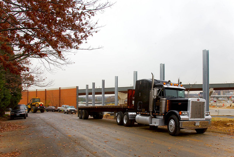 Peterbilt tractor pulling flatbed trailer waits at construction site after delivering materials. In immediate background are galvanized steel soldier beams embedded in concrete in earth to support brick acoustic/privacy fence. US Route 1 interchange with I495 Capital Beltway. Woodrow Wilson Bridge project, Alexandria, Virginia. November, 2006.