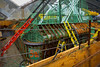 Steel forms and green epoxy coated reinforcing steel for cast in place reinforced concrete bridge pier base in foundation pit. Ladders provide access for workers to complete preparations for concrete placement. Piers for completed east side bridge are in left background. The curved portion at bottom of completed piers coincides with curved forms in foreground, and the ~45 degree joint shown is connection of top of pier base to lowest field precast concrete modules of V-shaped pier legs. Woodrow Wilson Bridge replacement, Potomac River between Virginia and Maryland, Capitol Beltway, I-95/I-495. November 2006.