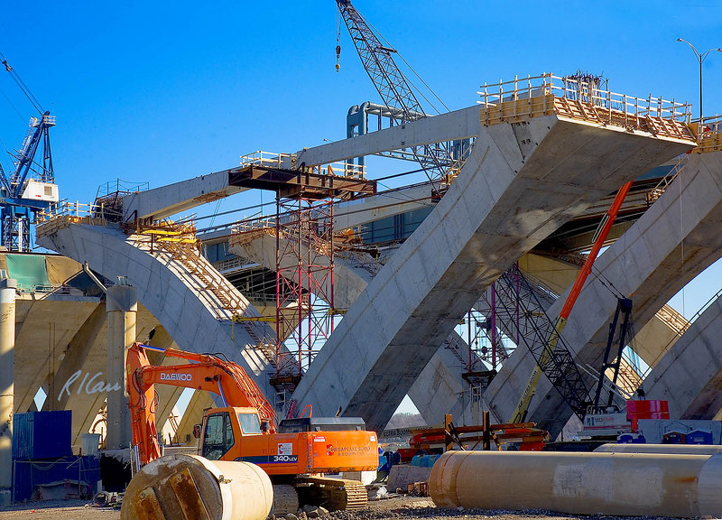 Precast concrete bridge construction: Precast post-tensioned concrete module, tied cantilevered arch section bridge piers, described as V-piers, support structural steel bridge stringers/girders/beams. Sloped arch sections consist of hollow field-precast reinforced concrete segments tied together by post-tensioned steel cables. Two piers in rear support completed south half of bridge, and two piers in foreground are being constructed for north half of bridge. Outward thrust of pair of arch sections is supported by two post-tensioned horizontal precast reinforced concrete tension tie beams, which are cast in two segments, temporarily supported by a steel truss scaffold erection tower, to be joined by cast in place concrete and then posttensioned. In foreground is Daewoo 340LCV track mounted backhoe/excavator. In midground is Link-Belt lattice boom track mounted crane. Beyond that is JLG Ultra Boom self-propelled telescoping hydraulic boom personnel lift. Woodrow Wilson Bridge replacement, Potomac River between Virginia and Maryland, Capitol Beltway, I-95/I-495. November 2006.
