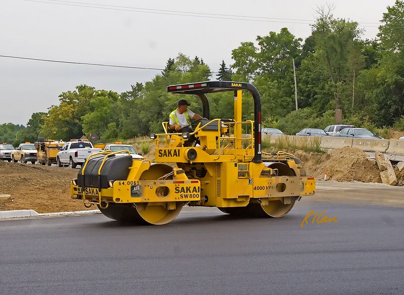 Asphalt construction equipment: Sakai SW800 dual drum asphalt vibratory roller/compactor compacts asphalt pavement for Geddes Road at Dixboro Road as part of Dixboro Bridge project, spanning the Huron River, Ann Arbor, MI, 2005.