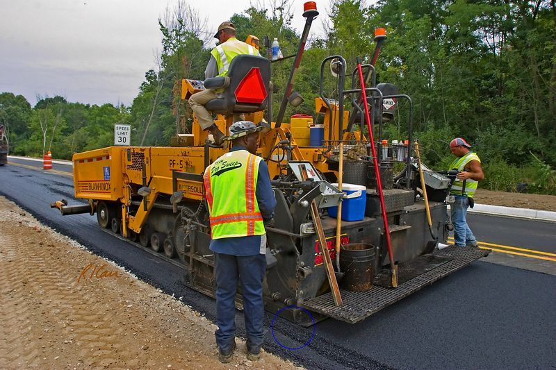 Asphalt paving construction: Blaw-Knox PF-5510 asphalt paving machine moves from right to left laying one lane of fresh asphalt concrete pavement from the asphalt concrete in its front hopper. The machine is operated and controlled by the operator in the upper seat. Note the fresh asphalt layer coming out the back of the paver, as circled at the lower left edge of the paver. Dixboro Rd, Ann Arbor, Michigan 2005.