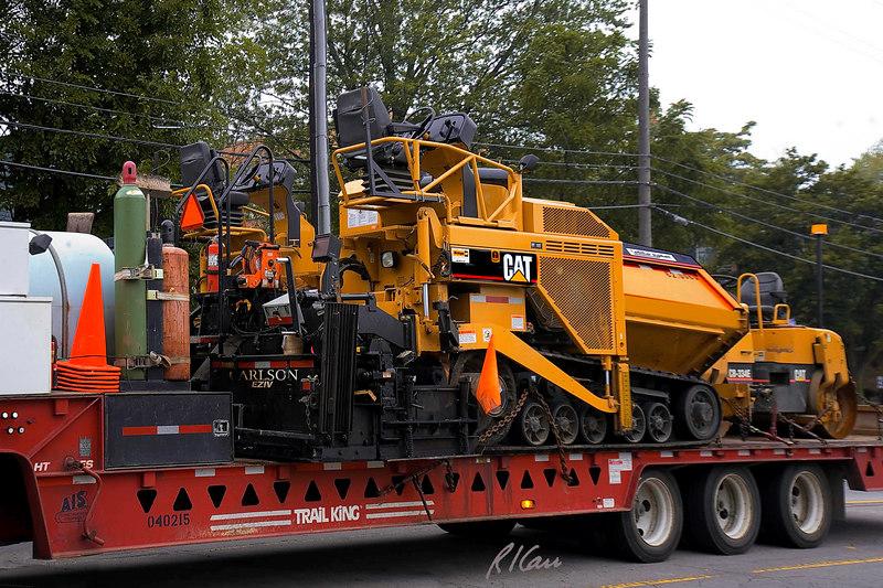 Asphalt construction equipment/truck: Kenworth truck tractor pulls Trail King low height equipment tender and transport trailer for Caterpillar AP-1055D asphalt paver and Caterpillar CB-334E vibratory roller/ compactor. Depot St, Ann Arbor, MI, August, 2006.