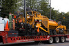 Asphalt construction equipment/truck: Kenworth truck tractor pulls Trail King low height equipment tender and transport trailer for Caterpillar AP-1055D asphalt paver and Caterpillar CB-334E vibratory roller/ compactor. Depot St, Ann Arbor, MI, August, 2006.