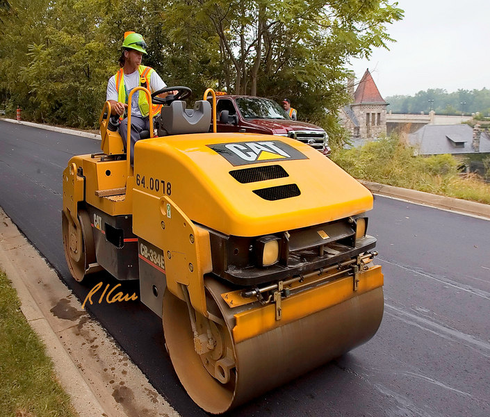 "Asphalt pavement construction/equipment: Caterpillar CB-334E vibratory asphalt compactor/roller rolls fresh asphalt on High Street. It has 51"" wide tandem steel drums, weighs 8,731 lb, 50 hp diesel engine and 4,140 vpm high-frequency vibration system. Ann Arbor, Michigan August 2006."