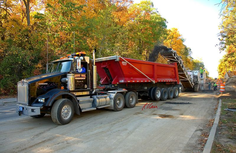 Asphalt construction: Roadtec RX900 asphalt cold milling machine strips old asphalt from Northbound lane and dumps into dump trucks, here a Kenworth with a Hardbox rear dump trailer, with its front end conveyor. Huron Parkway, Ann Arbor 2005.