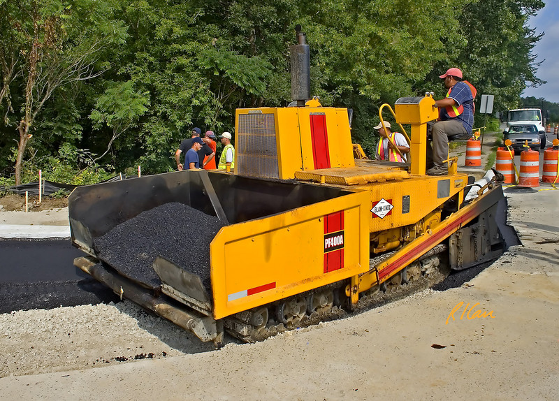 Asphalt paving construction: Blaw-Knox PF-400A asphalt paving machine moves from left to right laying one lane of fresh asphalt concrete pavement from the asphalt concrete in its hopper. The machine is operated and controlled by the operator in the upper seat. In this case the paver is laying asphalt pavement on top of the gravel base to build the curved right-turn entrance to Huron High School for vehicles travelling South on Huron Parkway.  Ann Arbor, Michigan 2005.