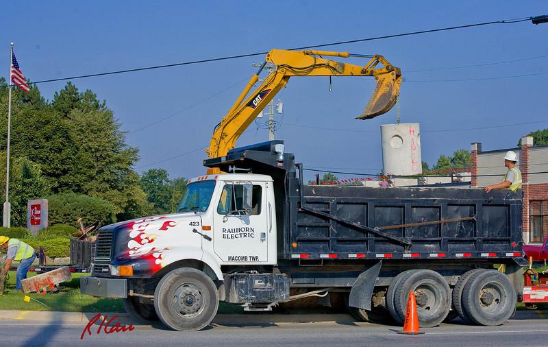 Caterpillar 308C CR backhoe unloads precast concrete from International truck/Rogers rear dump bed. Carpenter Rd, Ann Arbor, Michigan 2007.