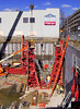 Concrete cast-in-place construction: Gang forms for cast-in-place (CIP) reinforced concrete deep foundation/basement walls. Gang forms are sets of large form panels attached and braced together and moved by crane from place to place to cast large sections of concrete. The vertical concrete wall at lower right was cast using the gang form in middle of photo, rotated 90 degrees. It has been lifted and rotated into its current position by the crane (see boom shadow) and cables attached to its top. It will probably be lifted and rotated to form the wall section to the immediate left of the one it recently placed. Another gang form is in place on the right wall against which the next wall section will be cast. Workers at lower right are finalizing the details at bottom of reinforcing steel in preparation for the form to be placed. Reinforcing steel is being erected for the far wall to follow the wall on the right. Still another gang form in the lower right corner of photo is still in place after casting the lower right corner of the basement. Ashley Terrace, Huron St, Ann Arbor, Michigan 2006