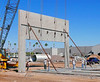 Precast concrete tilt-up construction: Reinforced concrete wall section has been pulled up at its top into near vertical position to form section of outside wall of building. Wall section is heavily reinforced concrete that was cast in horizontal position on top of floor slab of building, which alleviated the need for wall forms. It is lifted by steel cable, hooked to wall at a 8 points to provide force sufficient to break wall free from the slab beneath it and lift it into its final vertical position. Two point support from lifting beams/ harness and pulleys provide independent support to each lifting point. Pipe with screw jacks at end align the wall and support it against wind forces. Workers 3, 5, and 6, from left to right, hold chain/cable with which they will jerk out pens locking the lifting cables to the slab wall, and they will next pull to withdraw pens to separate lifting tools from the wall. Phoenix, Arizona, November 2006.