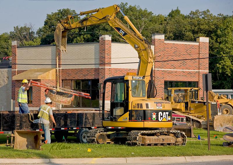 Caterpillar 308C CR backhoe unloads manhole concrete formwork from trailer. Carpenter Rd, Ann Arbor, Michigan 2007.