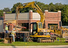 Caterpillar 308C CR backhoe unloads manhole concrete formwork from trailer. Carpenter Rd, Ann Arbor, Michigan 2007.
