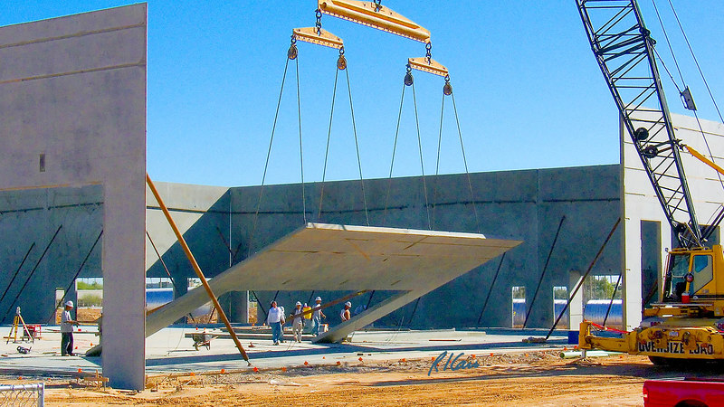 Precast concrete tilt-up construction: Reinforced concrete wall section is pulled up at its top into near vertical position to form section of outside wall of building. Wall section is heavily reinforced concrete that was cast in horizontal position on top of floor slab of building, which alleviated the need for wall forms. It is lifted by steel cable, hooked to wall at a 8 points to provide force sufficient to break wall free from the slab beneath it and lift it into its final vertical position. Two point support from lifting beams/ harness and pulleys provide independent support to each lifting point. Phoenix, Arizona, November 2006.