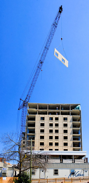 Manitowoc crane with luffing boom lifts precast concrete panel cladding panel into position on west side of midrise residential building. Ashley Terrace, Ann Arbor, Michigan April, 2007.