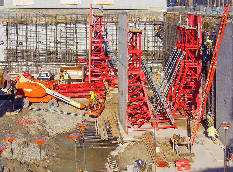 """Concrete cast-in-place construction: Gang forms for cast-in-place (CIP) reinforced concrete deep foundation/basement walls. Gang forms are sets of large form panels attached and braced together and moved by crane from place to place to cast large sections of concrete. The vertical concrete wall at lower right was cast using the gang form in middle of photo, rotated 90 degrees. It has been lifted and rotated into its current position by the crane. It will probably be lifted and rotated to form the wall section to the immediate left of the one it recently placed. Another gang form is in place on the right wall against which the next wall section will be cast. Workers at right are finalizing the details of reinforcing steel in preparation for the form to be placed. Reinforcing steel is being erected for the far wall to follow the wall on the right. In photo center is JLG telescoping boom man lift. The orange """"mushrooms"""" in extreme foreground are reinforcing rod caps to protect workers who might fall onto the ends of the vertical rods. Ashley Terrace, Huron St, Ann Arbor, Michigan 2006"""