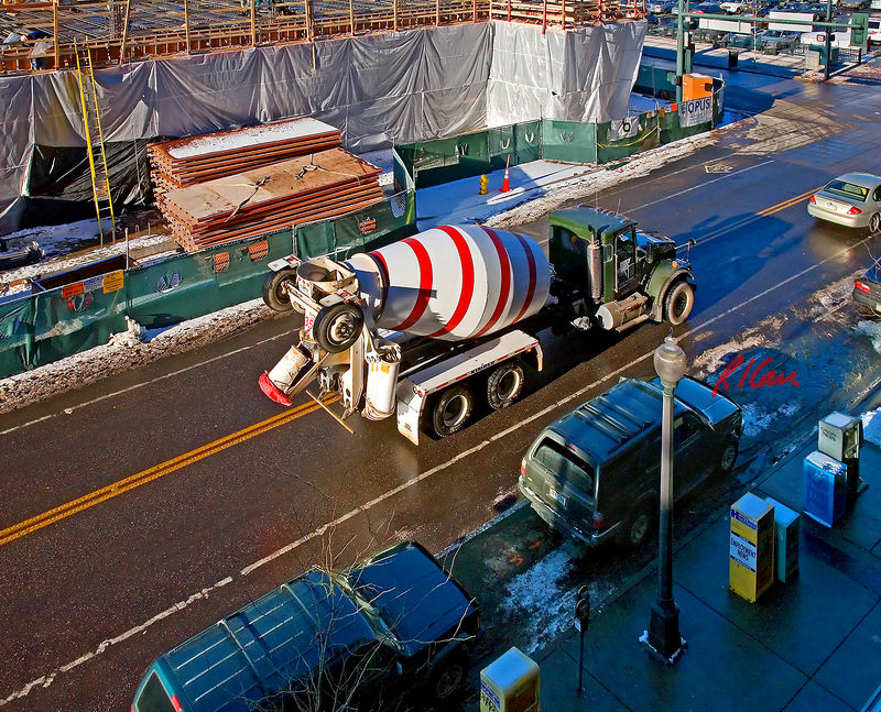 Concrete construction: Kenworthy chassis readymix concrete truck transports remote plant mixed concrete to construction site at top of photo, turning left at corner to opposite side of the site. Denver, Colorado December 2005.
