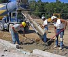 Concrete construction: Placing concrete footing at grade from ready-mix truck chute. Huron Village Shopping Center, Ann Arbor, 2002.
