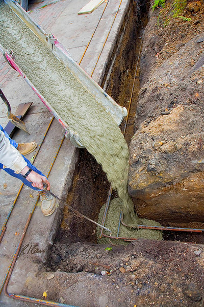 Cast-in-place concrete construction, reinforced: In lower half of photo, bent end of rebar is used to pull up bottom rebar in trench during concrete placement to achieve necessary concrete cover under rebar to protect it from soil/moisture/salts and produce bond between concrete and steel. Concrete is being placed through chute from ready-mix concrete truck. Depot Street, Ann Arbor, Michigan, October, 2006.