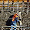Reinforced concrete structure construction: Shotcrete is mixed concrete sprayed against the back side form and around the reinforcing steel. This worker is screeding off excess shotcrete to form a vertical surface suitable for trowelling to a smooth surface. Pallazo, Westwood, Los Angeles, California, January 2006.