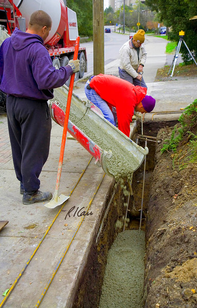 Cast-in-place concrete construction, reinforced: In center of photo, at far end of trench, bent end of rebar is used to pull up bottom rebar in trench during concrete placement to achieve necessary concrete cover under rebar to protect it from soil/moisture/salts and produce bond between concrete and steel. In addition, worker uses shovel to support rebar while concrete is placed. Concrete is being placed through chute from ready-mix concrete truck. Depot Street, Ann Arbor, Michigan, October, 2006.