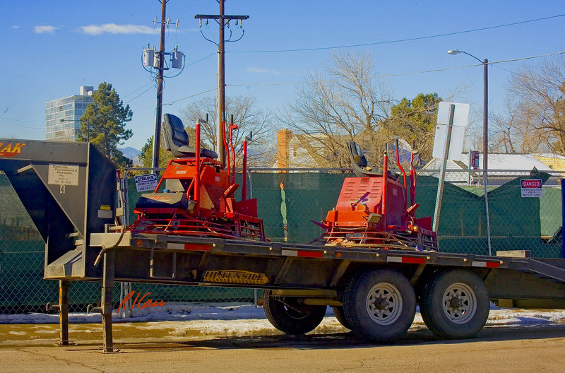 Allen Engineering Razorback Rider mechanical drive riding trowels sit on trailer awaiting use in finishing reinforced concrete elevated slabs of building. Monroe Pointe Building, Denver, Colorado, December, 2006.