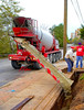 Concrete construction/readymix/placement: Advance front-discharge ready-mix concrete truck delivers and places concrete in trench. The mechanisms that position the concrete placing chute are all controlled by the truck driver from his driving position, which allows him to continually position truck and chute in the best placement location while placing concrete. <br />      Chute control mechanisms include the following: 1. Top of chute, where concrete is fed into chute, can be rotated horizontally through 180+ degrees with horizontal chain drive around chute top gear, to place concrete at any angle to side or in front of truck. 2. Hydraulic piston at vertical angle from truck front center supports and positions 1st section of chute vertically. 3. Hydraulic pistons parallel to chute on both sides at joints between sections 1 and 2 and sections 2 and 3 fold chute up out of driver's way when truck is driven to and from job. Depot Street, Ann Arbor, Michigan, October, 2006.