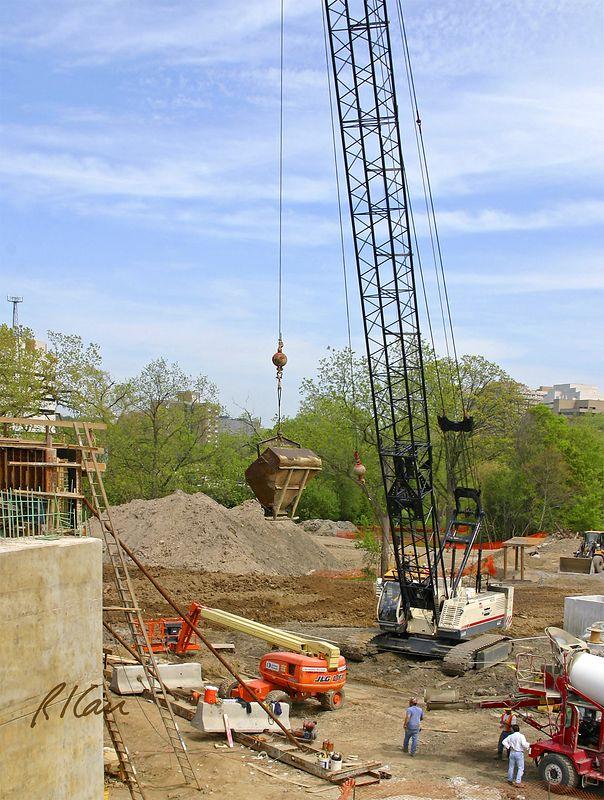 Bridge concrete construction: Terex American HC110 hydraulic lattice boom crawler crane lifts full concrete bucket (laydown bucket) to place concrete in bridge pier. Broadway Bridge, Ann Arbor, 2003.