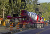 Concrete construction, placement, ready-mix: Front-chute concrete ready-mix truck backs up into position to place concrete for drilled piers that support steel soldier beams for retaining wall. Two axles of the five rear axles support the concrete, along with the front steering axle. A flag person is controlling adjacent traffic with a two-sided stop/slow sign (not shown). Huron Parkway, Ann Arbor, Michigan, August 2005.