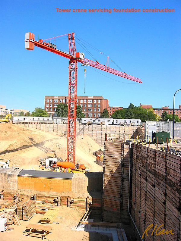 Construction crane: Tower crane servicing a deep basement excavation, with tied-back soldier-beam timber soil support.
