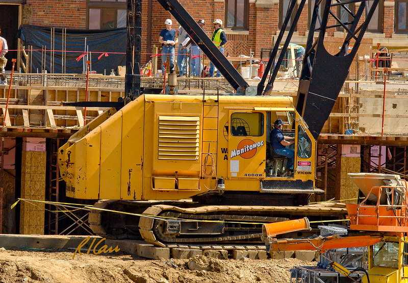 Cab of Manitowoc 4000W 150 ton track mounted lattice boom crane with flying jib. Construction site for addition to university dormitory. Crane and its cab, including rear counterweights, can rotate 360 degrees. Note the metal rods extending from brackets on the end track drive rollers, to which yellow caution tape has been attached to mark the rotating counterweight hazard area. Mosher Jordan Renovation and New Dining Center, University of Michigan, Ann Arbor, March 2007.