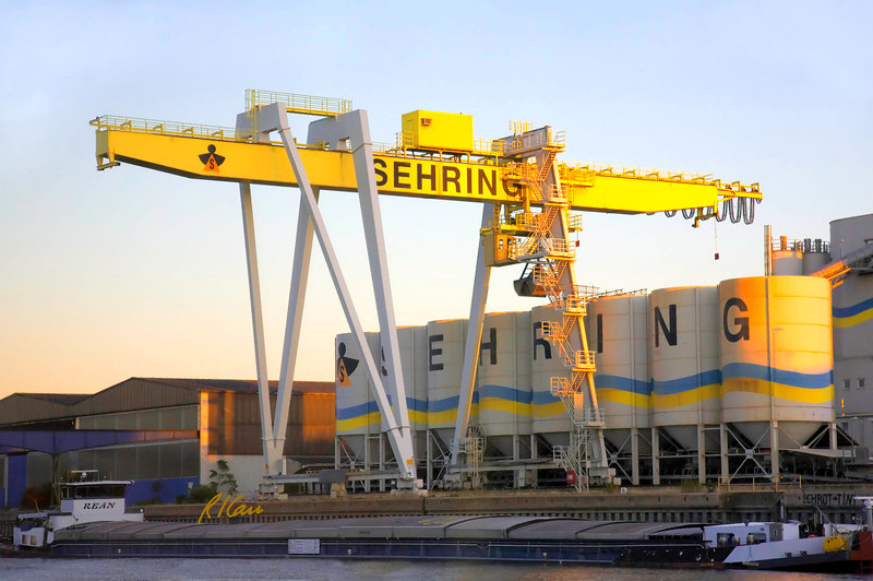 Marine/port/clamshell crane: Large overhead crane rides on hollow beam, itself supported by gantries riding on rails parallel to river and unloads bulk material from barge (as shown here, with cargoes covers closed) using clamshell bucket and places it in silos. Rhine/Main/Danube Canal near Wertheim, Germany August 2006