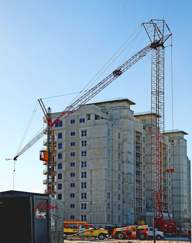 Building/vertical construction, crane:  Manitowoc track crane with open lattice boom and long open lattice luffing jib(tilted down here) building multi-story reinforced concrete structure and concrete block residential building. Fort Pierce Beach, Florida, November 2005.
