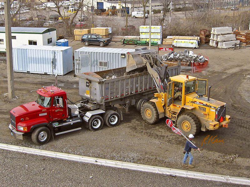 Pavement construction demolition: Volvo L90D wheel front-end loader dumps debris into rear dump truck. Broadway Bridge, Ann Arbor, 2003