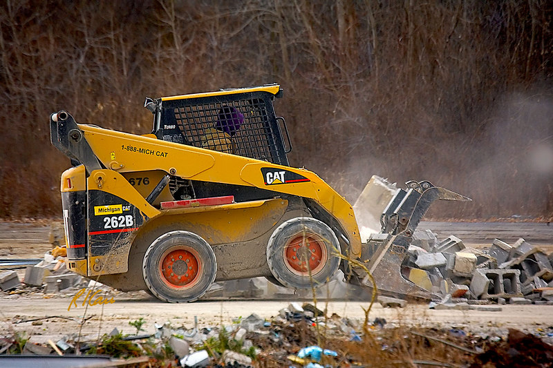 Caterpillar 262B skid-steer tractor with grappler bucket rakes concrete block building debris into a pile to be loaded into dumpster by a backhoe. Washtenaw near Huron Parkway, Ann Arbor, Michigan. January, 2007.