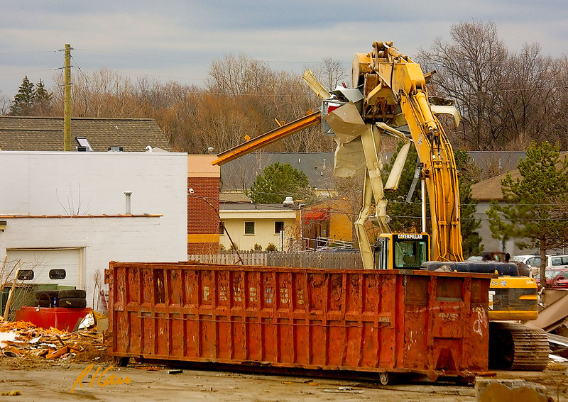 Caterpillar 345B backhoe with grappler bucket picks up sheet metal debris from building demolition and places it in large dumpster, to be hauled away. Washtenaw near Huron Parkway, Ann Arbor, Michigan. January, 2007.