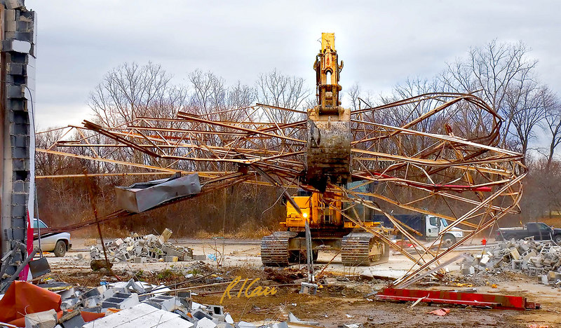 "Caterpillar 345B backhoe lifts a giant ""hand full"" of roof open steel web joists with its grappler bucket and is turning and traveling to the debris dumpster into whiich it will cram the joists along with other steel demolition debris. Washtenaw near Huron Parkway, Ann Arbor, Michigan. January, 2007."